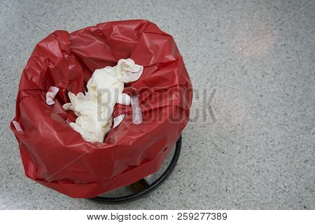 Used surgical gloves, gauzes and syringe in a red garbage bin for biohazard disposal stock photo