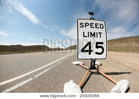 a 45 mile per hour speed limit sign on a highway in the desert. shot with a fisheye lens for a fun distorted image stock photo