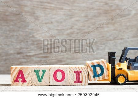 Toy forklift hold letter block d to complete word avoid on wood background stock photo