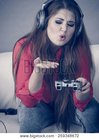 Woman being angry while playing video game holding gaming pad and complaining. stock photo