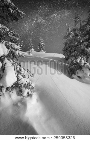 Mountain valley covered with fresh snow in a light of rising moon with. Fantastic milky way in a starry sky. Christmas winter night. Black and white stock photo
