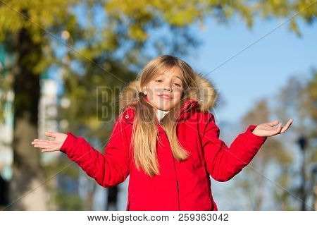 Happy small girl in autumn park. Small girl did it in mistake. Oops. Even the wisest of us can make a mistake. The first touches of autumn. Enjoy happy childhood. stock photo