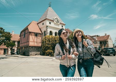 two good friends crossing the road and laughing with each other while having a sightseeing in a lovely town. stock photo