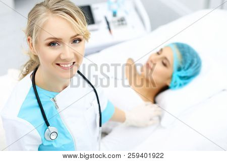 Female doctor and young woman patient in hospital. Physicians examine girl lying at the bed, view from above stock photo