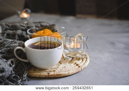 Still life details in home interior of living room. Cup of tea and dried apricots on a table, candles and knited blanket. Cozy mood autumn or winter in a lazy weekend . stock photo