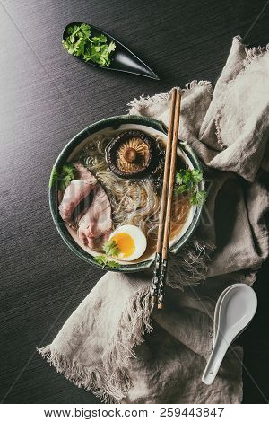 Traditional Japanese Noodle Soup with shiitake mushroom, egg, sliced beef and greens served in ceramic bowl with wooden chopsticks and white spoon on cloth over dark background. Flat lay, space. stock photo