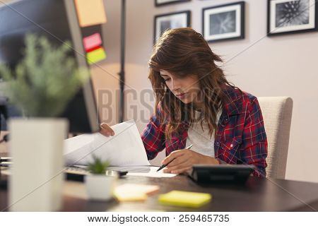 Young woman reviewing documents, working late in a home office stock photo