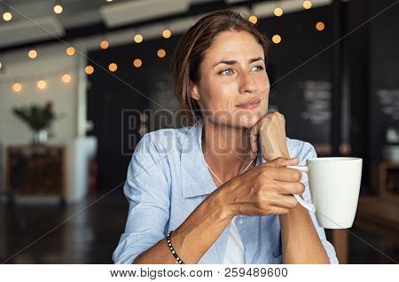 Thoughtful mature woman sitting in cafeteria holding coffee mug while looking away. Middle aged woma
