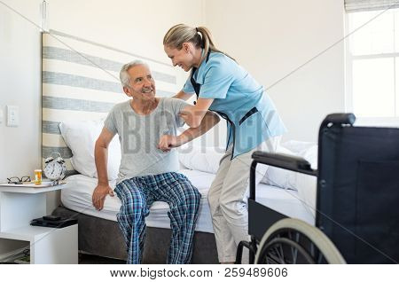Smiling nurse assisting senior man to get up from bed. Caring nurse supporting patient while getting