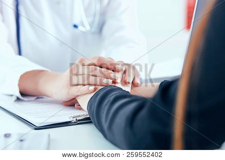 Friendly female doctor's hands holding female patient's hand for encouragement and empathy. There is always hope for recovery. stock photo