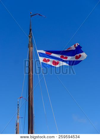 The Frisian flag waves proudly in the wind in the mast of a sailboat in the Dutch province of Friesland stock photo