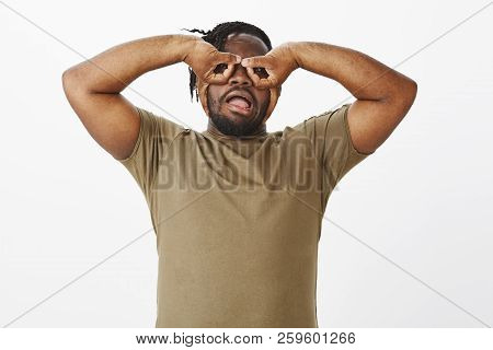 Waist-up shot of funny carefree african-american guy in olive t-shirt, holding hands over eyes and making faces, mimicking goggles or eyewear while fooling around over grey background stock photo
