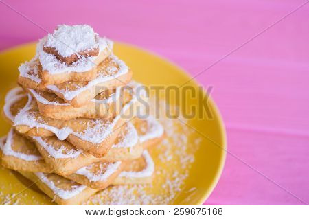 Closeup Christmas tree made from cookies in form of stars with coconut chips on yellow plate. Winter homemade baked dessert. stock photo