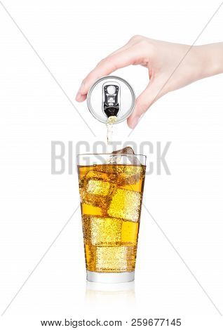 Female hand pouring orange energy soda drink from aluminium can to glass on white background stock photo