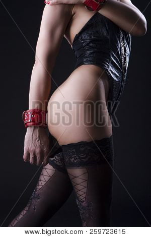BDSM Concepts. Back View of Caucasian Female in Sexy Leather Bodysuit Prepared for Sado-Masochism Play. Touching Buttocks. Over Black. Vertical Orientation stock photo