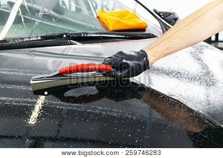 A man cleaning car with microfiber cloth, car detailing (or valeting) concept. Selective focus. Car detailing. Cleaning with sponge. Worker cleaning. Microfiber and cleaning solution to clean stock photo