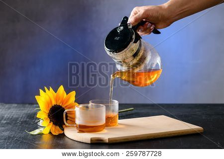 Woman hands pour asian tea. Japanese, Chinese and Thai traditional tea ceremony with pot and small cups. Herbal green and black Chinese tea leaves, aromatic drink, authentic stock photo