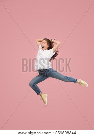 Freedom in moving. Mid-air shot of pretty happy young woman jumping and gesturing against pink studio background. Runnin girl in motion or movement. Human emotions and facial expressions concept stock photo
