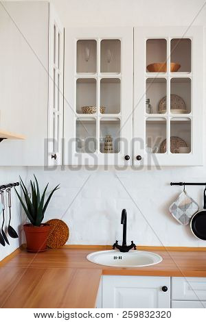 White kitchen sink and black water tap in the kitchen. The interior of the kitchen room of the apartment. Built-In Appliances. Kitchen Appliance. Domestic Appliances. stock photo