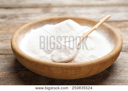 Plate with baking soda on wooden background stock photo