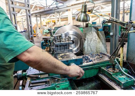 The worker, the man, makes mechanical actions of the machine control. Turning work in production stock photo