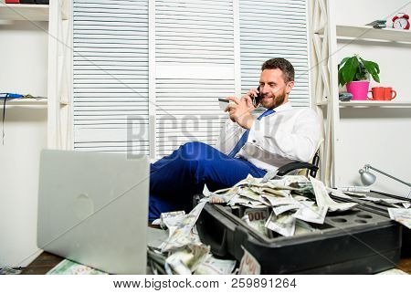 Man hold plastic bank card. Man successful businessman phone conversation ask service. Businessman rich bearded guy sit office with lot of cash money. Bank loan or credit. Get cash in few minutes stock photo