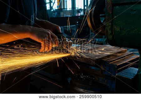 The worker polishes the metal with a grinding machine and sparks close-up stock photo