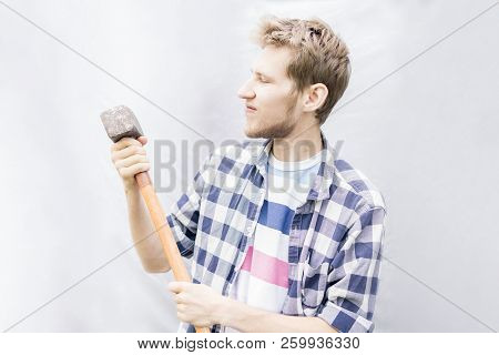 angry concept, young man in casual holding huge massive hammer isolated with copy space stock photo