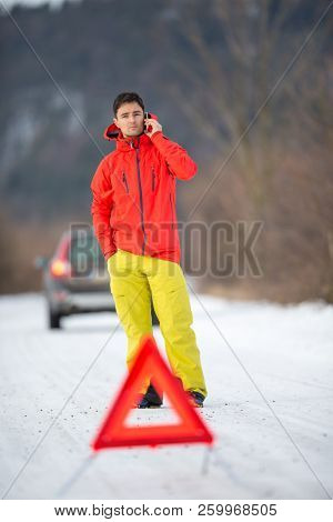 Young man calling car assistance service after his car has broken down on a cold winter day stock photo