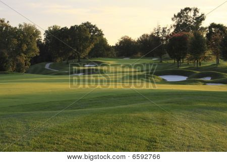 Golf course at sunset in autumn with fairway and bunkers stock photo