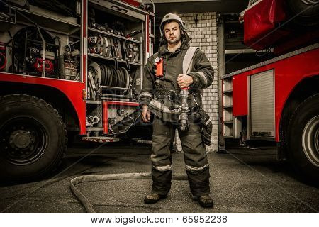 Firefighter near truck with equipment with water water hose over shoulder  stock photo