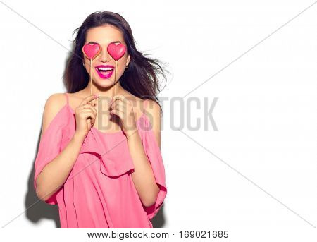 Beauty joyful Young fashion model Girl with Valentine Heart shaped cookies in her hands. Love Concep