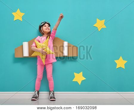 Little child girl in an astronaut costume is playing and dreaming of becoming a spaceman. Portrait o