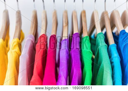 Fashion clothes on clothing rack - bright colorful closet. Closeup of rainbow color choice of trendy