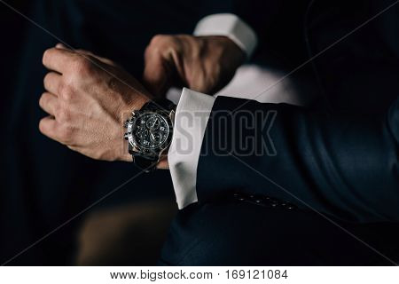 beautiful muscular black watch on the hand of man in suit