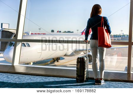 Travel tourist standing with luggage watching sunset at airport window. Unrecognizable woman looking