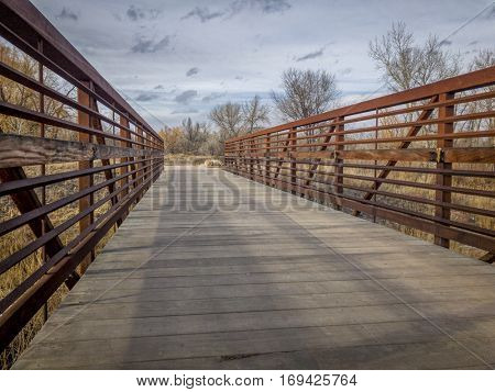Footbridge on a recreational and commuting bike trail along the Poudre River in Fort Collins, Colorado, typical winter scenery stock photo