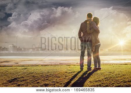 Happy romantic loving couple at the lake hugging and looking away love and relationships concept