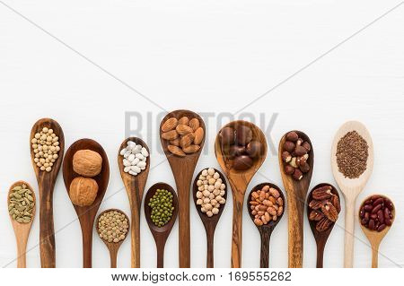 Different kind of beans and lentils in wooden spoon on white wood background. mung bean groundnut walnuts macadamia almond soybean red kidney bean black bean sesame corn red bean and brown pinto beans stock photo
