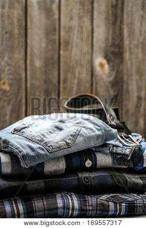 folded men's shirt in the box and the belt with jeans on wooden background , concept of style and fashion stock photo