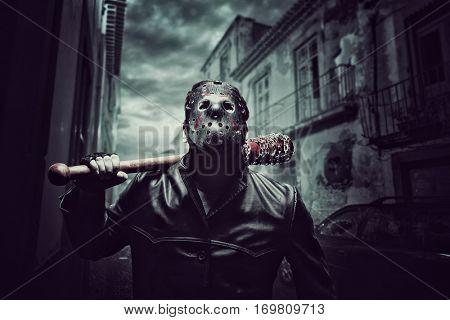 Psycho man in hockey mask with bloody baseball bat stock photo