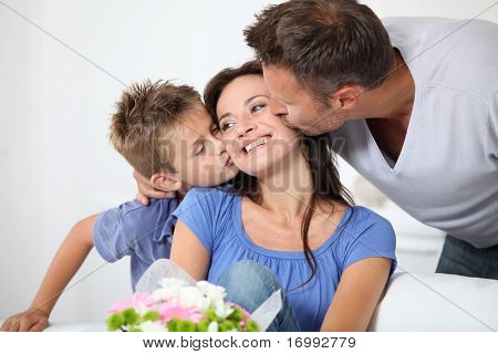 Father and son kissing mother on her birthday stock photo