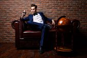 Imposing well dressed man in a luxurious apartments with classic interior. Luxury. Men's beauty, fas