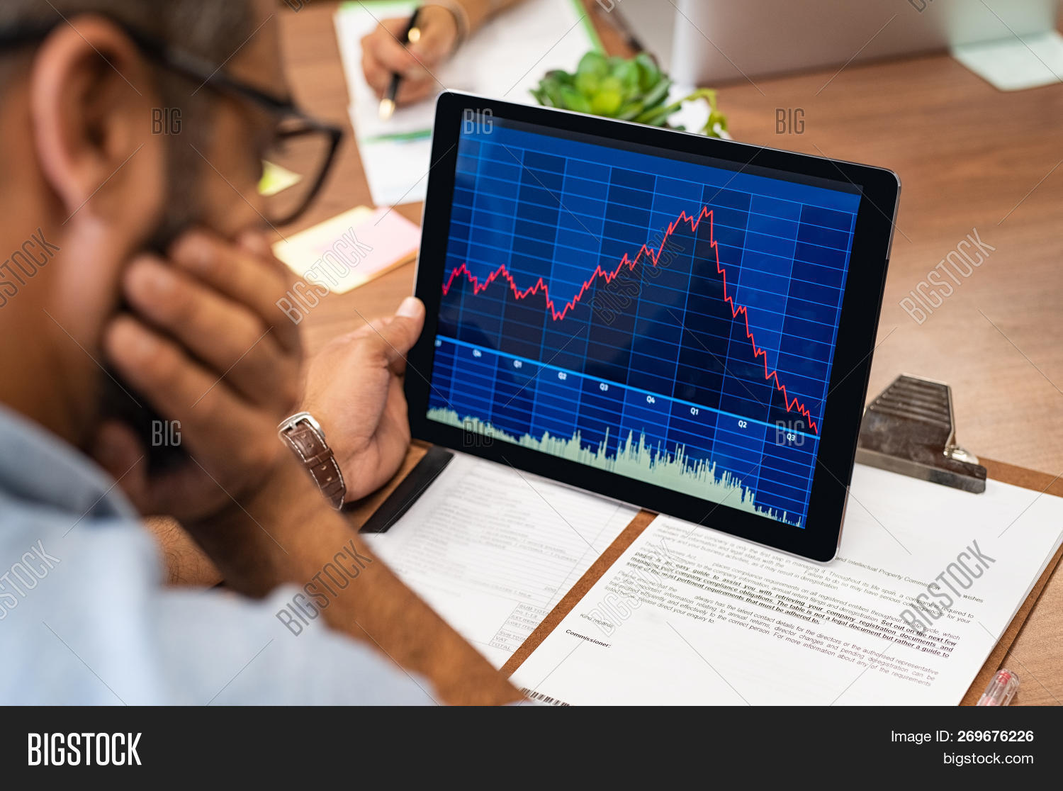 Closeup of a stock market broker working with graphs on digital tablet at office. Rear view of stock