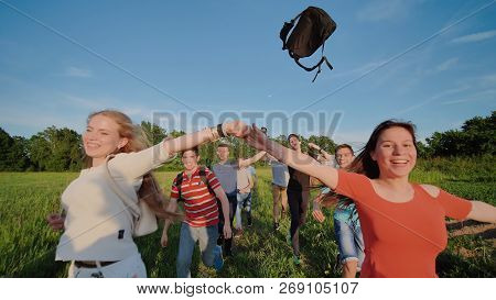 Happy senior pupils flee and toss their portfolios against the sunset. Happy ending school days. Slow motion. stock photo