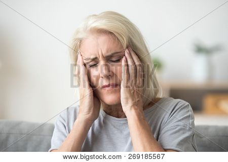 Upset older woman touching temples aching head feeling strong he stock photo