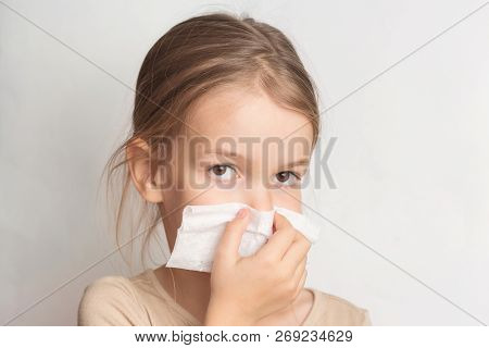 Runny nose in children. A child blows his nose in a handkerchief. stock photo