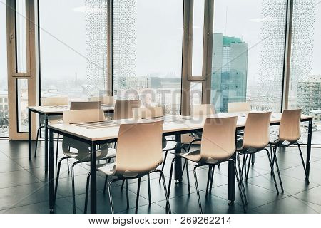 Coffee break. Negotiation table. Nobody. Office dinner with full length windows. Lunch time in office. Break time. Table with chair and food stand. Office kitchen