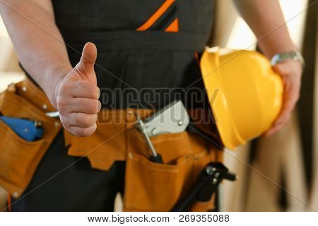 Hand of worker in yellow helmet show confirm sign with thumb up at arm portrait. Manual job DIY inspiration joinery startup idea fix shop hard hat industrial education profession career concept stock photo
