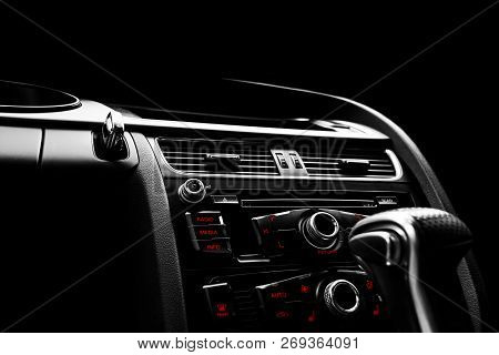 Modern Luxury sport car inside. Interior of prestige car. Black Leather. Car detailing. Dashboard. Media, climate and navigation control buttons. Sound system. Modern car interior details. Black and white stock photo